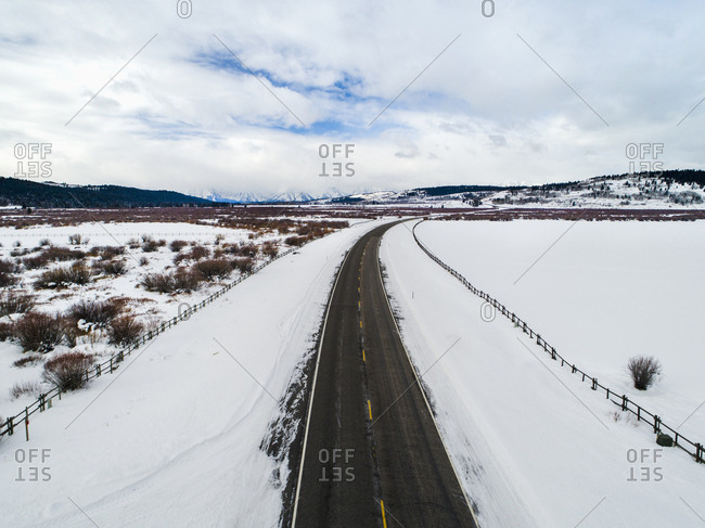 Empty road amidst snow covered landscape against cloudy sky