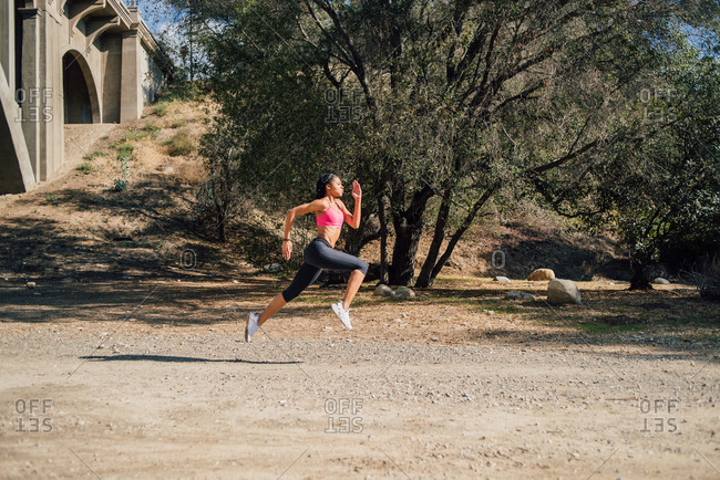 Determined female athlete jogging on road during sunny day