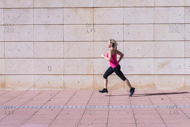 Full length side view of female athlete running on sidewalk against wall.