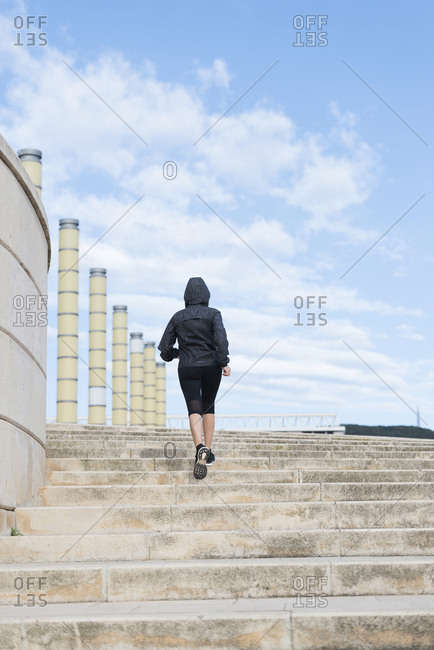 A female mature runner running up a set of stairs in Barcelona.