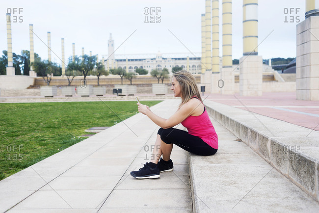 Mature fit woman in sportswear sitting on step and browsing smartphone during the break on street