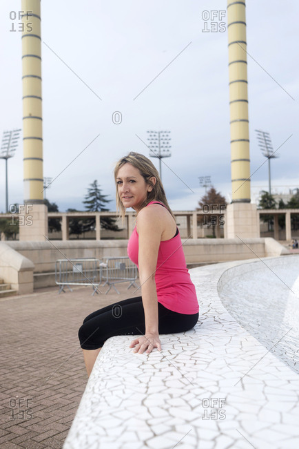 Blonde caucasian woman with sportswear sitting in a pavement on the street
