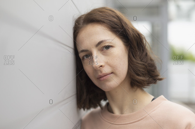 Portrait serene woman leaning against wall
