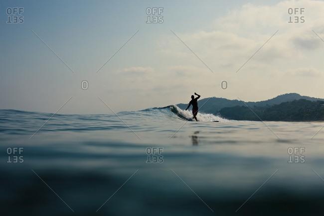 Surfer riding ocean wave, Sayulita, Nayarit, Mexico