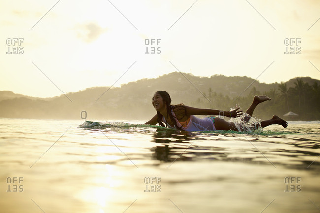 Happy female surfer paddling out in ocean on surfboard, Sayulita, Nayarit, Mexico