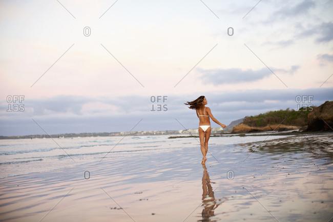 Carefree woman in bikini running on beach, Sayulita, Nayarit, Mexico