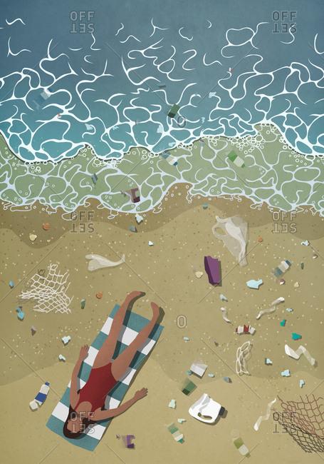 Litter surrounding woman sunbathing on ocean beach