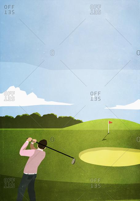 Man golfing on sunny golf course