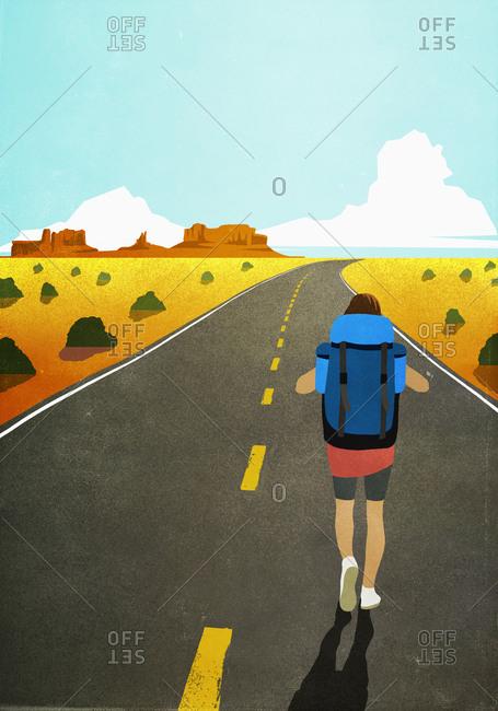 Female backpacker walking on remote, arid desert road