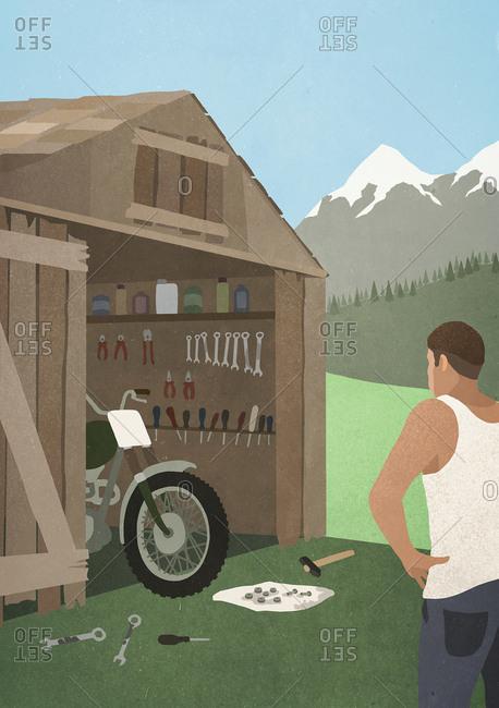 Man standing at garage shed, fixing motorcycle
