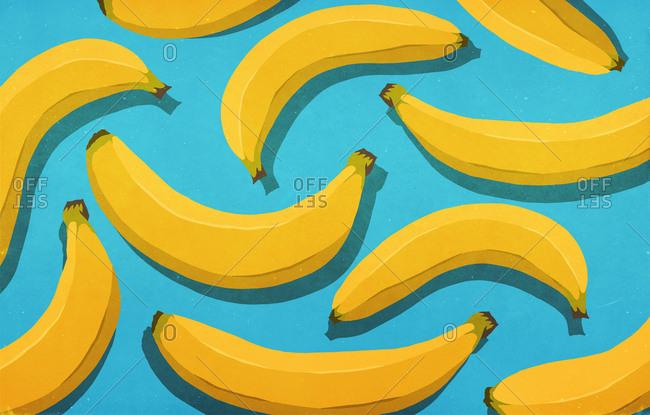 Vibrant, unpeeled yellow bananas on blue background
