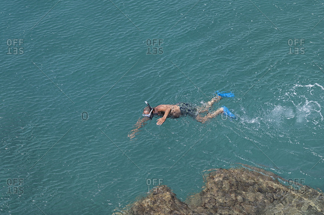 Man snorkeling in sunny, turquoise ocean, Spotorno, Liguria, Italy