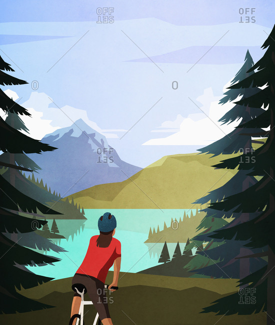 Female mountain biker looking at idyllic, tranquil mountain lake view