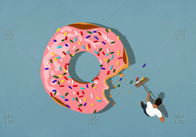 Man with broom sweeping up donut sprinkles