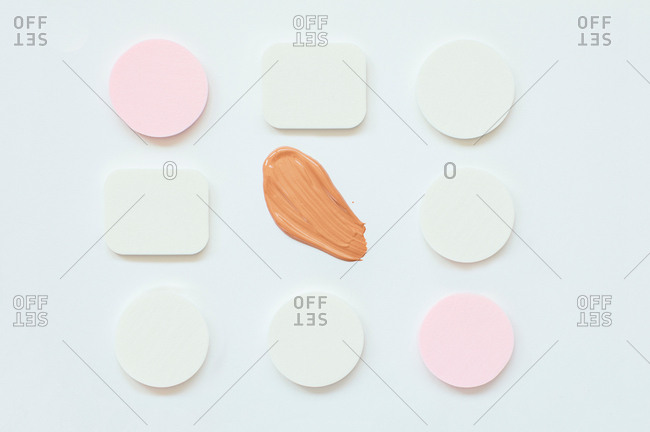 Overhead view of makeup sponges and foundation on a white background