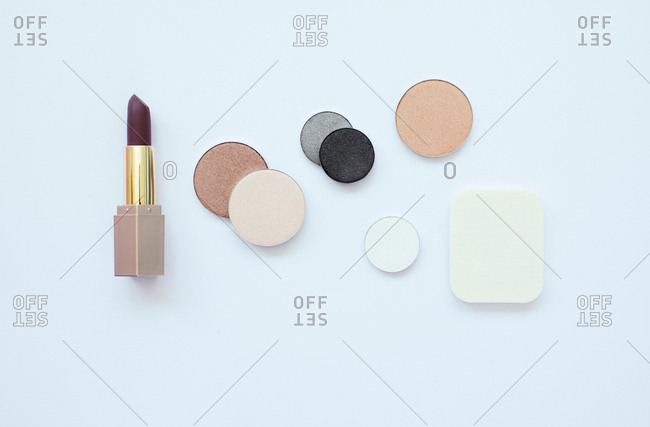 Flatlay of dark lipstick and pressed powders on a white background