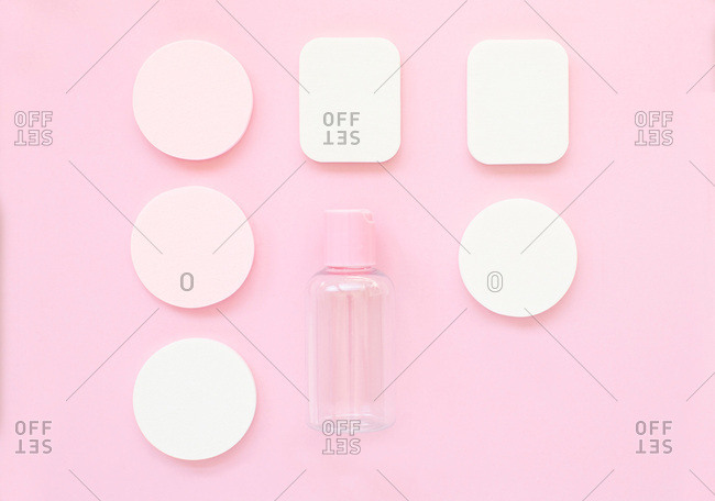 Overhead view of makeup sponges and bottle arranged on a bright pink background