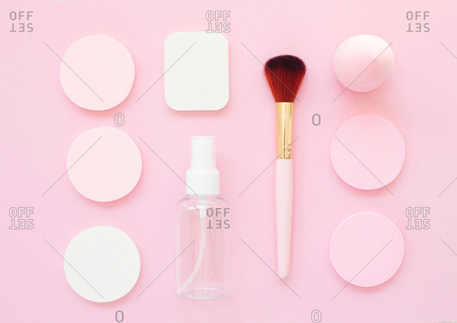 Overhead view of makeup tools and round sponges organized on a bright pink background