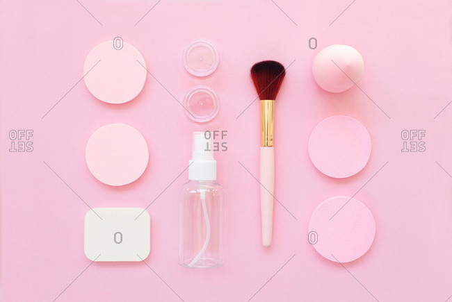 Overhead view of makeup tools organized on a bright pink background