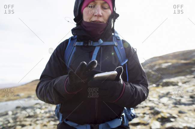 Woman using smart phone while hiking