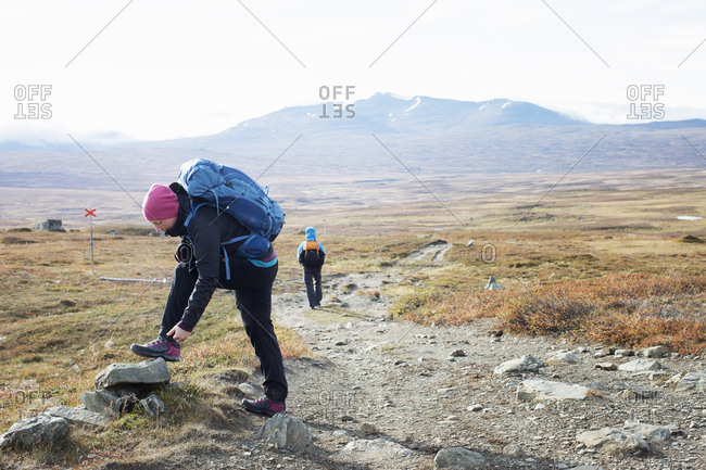 Woman fixing shoe during hike
