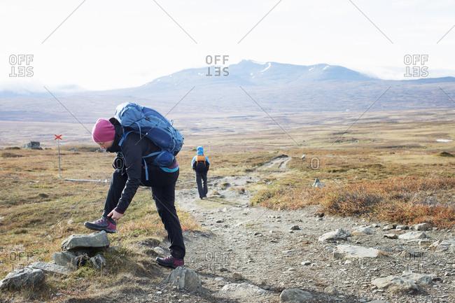 Woman fixing shoe during hike