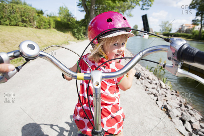Girl cycling with her helmet on