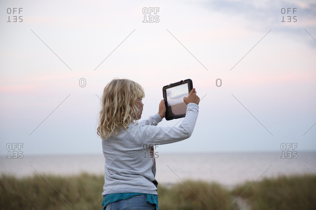 Girl taking photograph with tablet PC