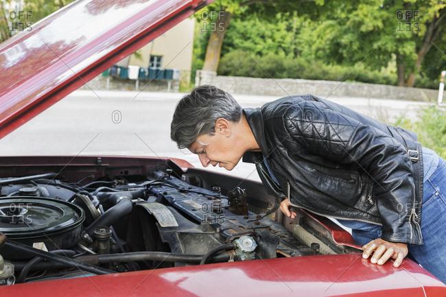 Mature woman checking under car bonnet