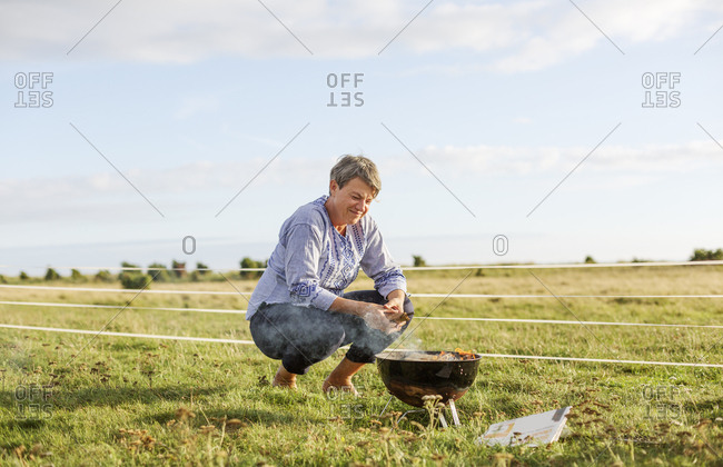 Woman crouching by brazier in field