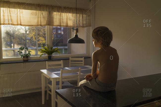Boy sitting on kitchen bench