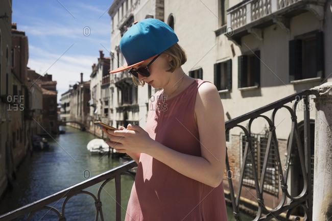 Teenage girl standing on a bridge in Venice,  Italy