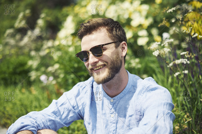 Smiling mid adult man wearing sunglasses by flowers