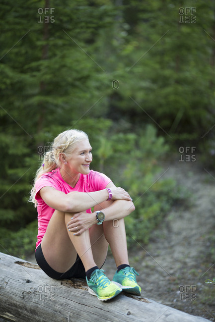 Woman smiling on log in forest