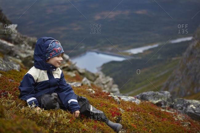 Boy sitting on mountain