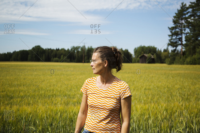 Woman standing by field in countryside in Dalarna,  Sweden