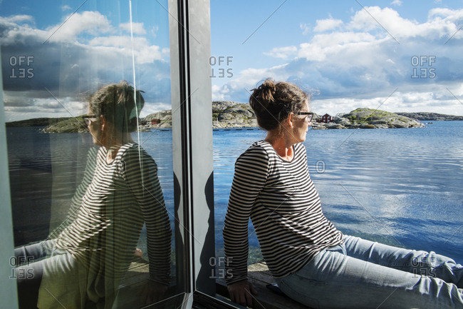 Mature woman sitting on balcony over the sea