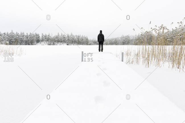 Mature woman standing next to frozen lake in Ostergotland,  Sweden