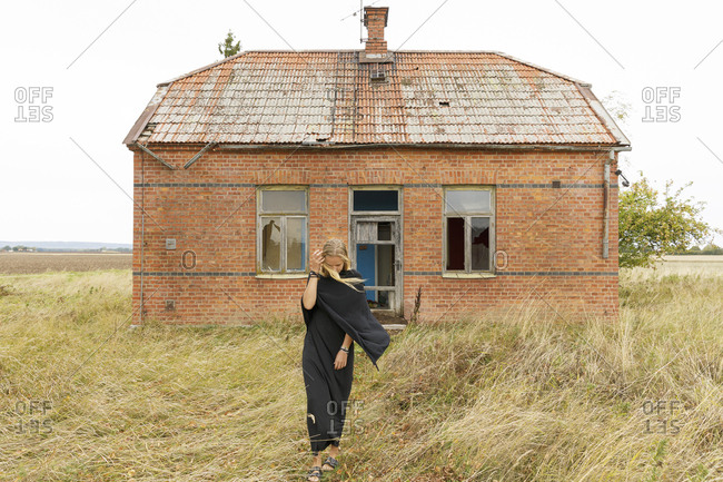 Woman wearing black by abandoned house