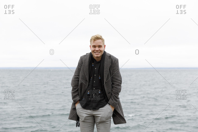 Smiling man wearing gray coat by Vattern lake in Stora Lund Nature Reserve,  Sweden