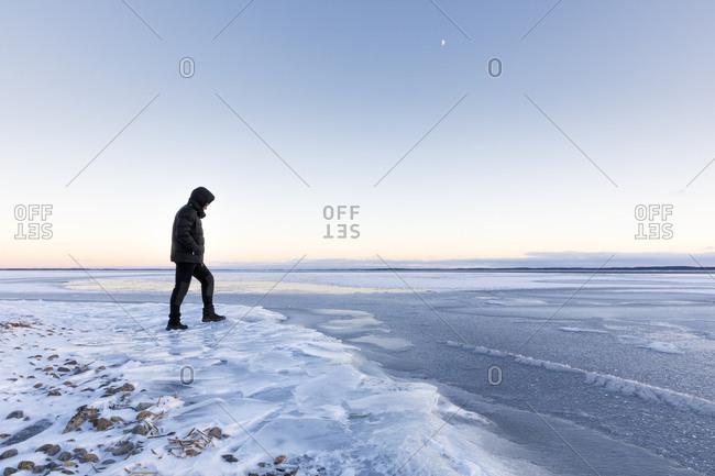 Man walking on frozen Glan lake at sunset in Ostergotland,  Sweden