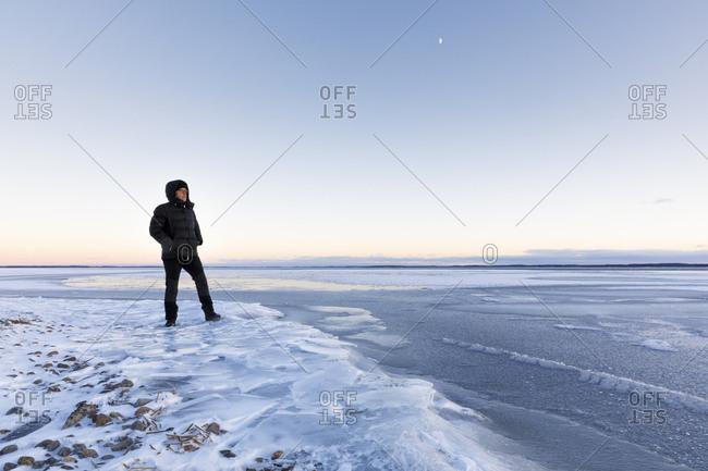 Man standing on frozen Glan lake at sunset in Ostergotland,  Sweden