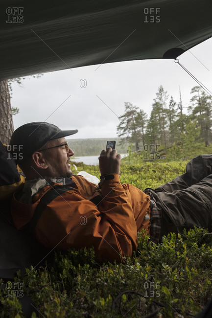 Man using smart phone in tent