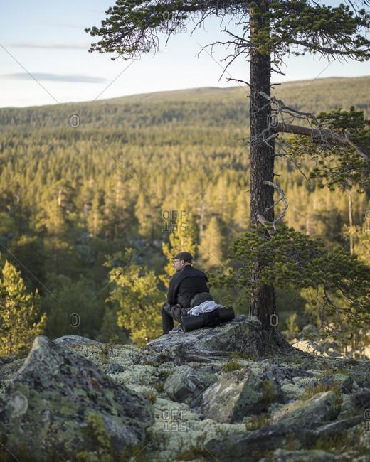 Man sitting on rock in Tofsingdalen Nature Reserve in Sweden