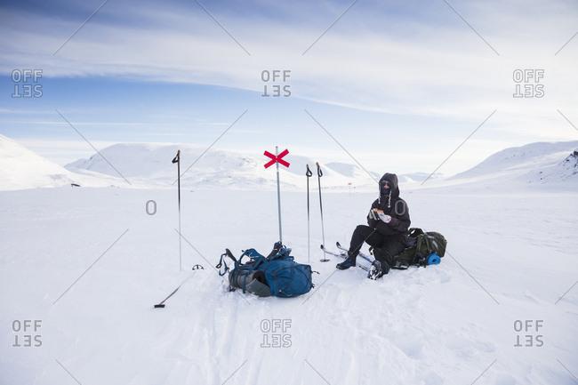 Woman resting on Kungsleden trail in Lapland,  Sweden