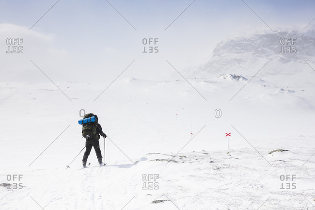 Woman skiing by mountains on Kungsleden train in Lapland,  Sweden