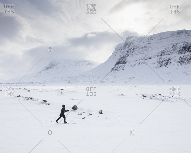 Woman skiing by mountains on Kungsleden trail in Lapland,  Sweden