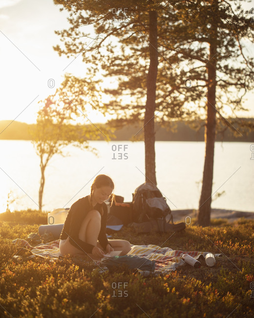 Young woman reading at sunset by Lake Norra Bredsjon,  Sweden