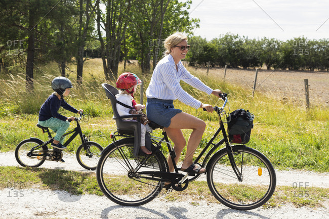 Mother cycling with her children on rural road