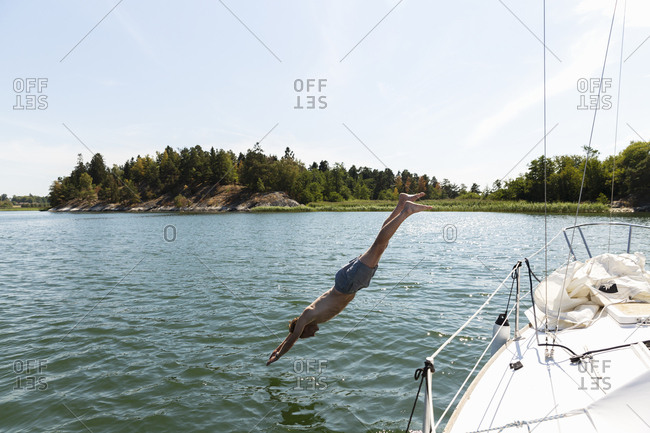 Man diving into sea off yacht